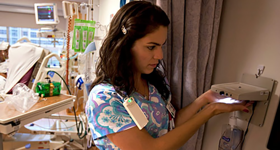 R.N. holds her hands under sensor before washing them, activating green light. © University of Florida Health, used with permission. [Originally published in: The Insider, University of Florida College of Medicine; April 2009]